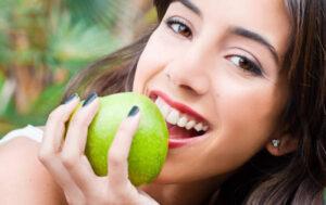 ragazza sorridente intenta a mordere una mela verde