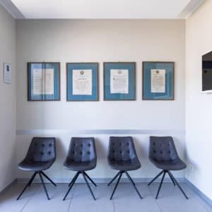 sala d'attesa con quattro poltroncine e quattro quadri alla parete