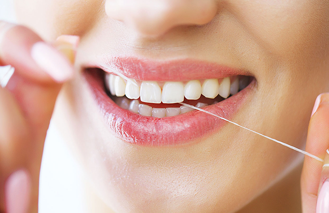 estetica bocca di donna sorridente che passa il filo interdentale