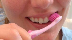 ragazza che usa lo spazzolino per pulire i denti
